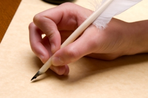 Photograph of a hand writing with a quill