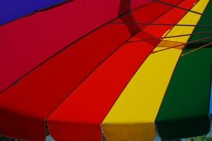 Photo of rainbow-striped umbrella. Credit to zenia.