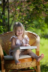 Little girl reading book sitting in wicker chair outdoor in summ