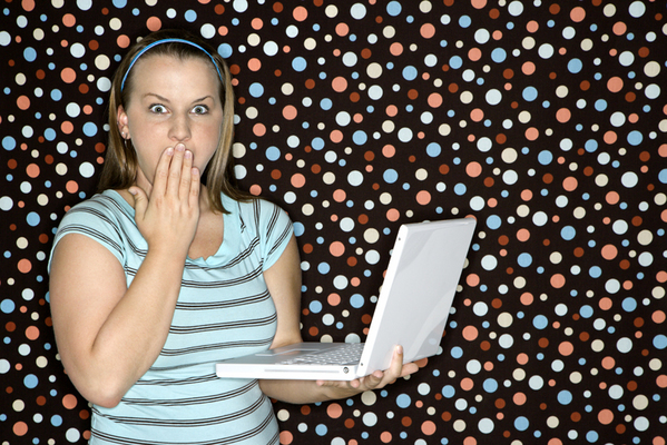 Woman with laptop looking shocked.